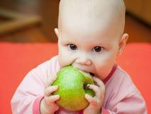 桃红色夹克的小婴孩吃绿色苹果 库存图片