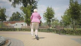 桃红色夹克的快乐的可爱的资深妇女使用滑行车,当乘坐在公园时 现代妇女,新一代 股票视频
