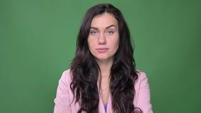 桃红色夹克轮的年轻深色的女实业家对诱惑照相机和手表入在绿色背景的照相机 股票视频