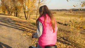 桃红色夹克骑马自行车的女孩,拿着方向盘用他的在秋天路的手 慢的行动 股票视频