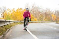 桃红色夹克骑马路自行车的少妇在高速公路在冷的秋天天 健康生活方式 免版税图库摄影