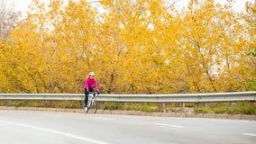 桃红色夹克骑马路自行车的少妇在高速公路在冷的秋天天 健康生活方式 库存图片
