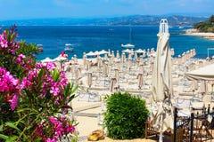 桃红色夹竹桃花、海滩与伞和蓝色海 库存照片