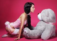 桃红色女用贴身内衣裤的诱人的嬉戏的妇女有玩具熊的 免版税库存照片