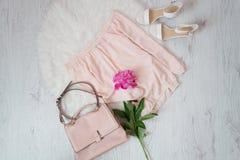 桃红色女衬衫、袋子、鞋子和牡丹花束  时兴的概念,在背景的白色毛皮 免版税库存照片