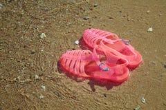桃红色妇女的在海岸的果冻凉鞋 夫人舱内甲板结冻夏天海滩鞋子 免版税库存照片