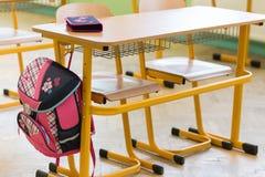 桃红色娘儿们书包和笔匣在一张书桌上在一间空的教室 日第一所学校 免版税库存照片