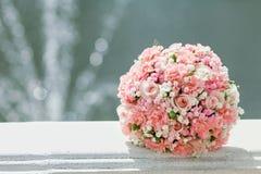 桃红色婚礼花束喷泉的背景的新娘 库存图片