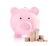 桃红色存钱罐和堆金钱硬币 库存图片