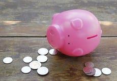 桃红色存钱罐和硬币在木地板上 免版税图库摄影
