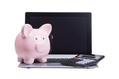 桃红色存钱罐和计算器在膝上型计算机 免版税图库摄影