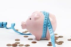 桃红色存钱罐有测量磁带的和在很多在白色背景的便士附近 免版税库存照片