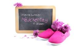桃红色孩子鞋子和花在文字黑板前面与 库存照片