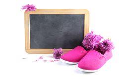 桃红色孩子鞋子和花在文字黑板的frot与 免版税库存照片