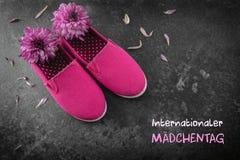 桃红色孩子鞋子和花在黑暗的板岩背景,德国te 图库摄影
