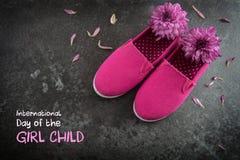 桃红色孩子鞋子和花在黑暗的板岩背景,文本天 免版税库存照片