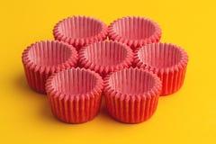 桃红色小杯形蛋糕盘子持有人的安排在黄色的 图库摄影