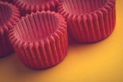 桃红色小杯形蛋糕盘子持有人的安排在黄色的 免版税库存图片