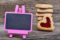 桃红色小黑板用在桌上的心脏曲奇饼 免版税库存图片