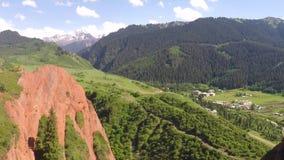桃红色岩石空中录影与缺乏植被和遥远的积雪的峰顶的 股票录像