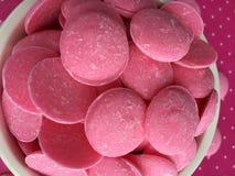 桃红色巧克力糖在桃红色圆点背景熔化 库存图片