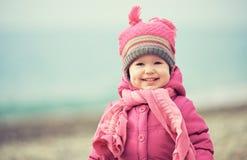 桃红色帽子和围巾的愉快的女婴笑 免版税库存图片