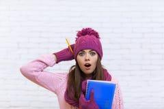 桃红色帽子学生的可爱的震惊十几岁的女孩震惊拿着文件夹铅笔 免版税库存照片