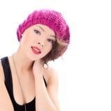 戴桃红色帽子的俏丽的微笑的妇女 免版税库存图片