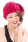 戴桃红色帽子的俏丽的微笑的妇女 库存照片