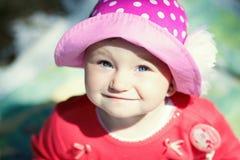 桃红色帽子的小女孩在一个晴天 图库摄影