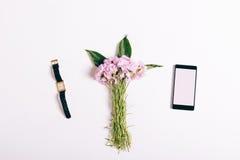 桃红色康乃馨、手机和女表小花束  免版税库存图片