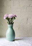 桃红色康乃馨和绿色花瓶 库存图片
