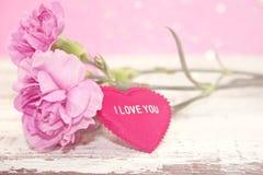 桃红色康乃馨开花与在土气白色木桌上的心脏 免版税图库摄影