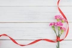 桃红色康乃馨开花与红色丝带的花束 库存图片