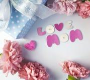 桃红色康乃馨花和礼物盒的愉快的母亲节概念 免版税库存图片