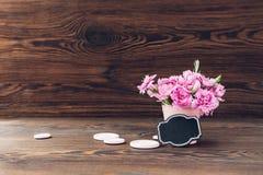 桃红色康乃馨花束在木背景的花瓶开花 文本的空的空间 免版税库存图片