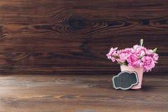 桃红色康乃馨花束在木背景的花瓶开花 文本的空的空间 图库摄影