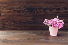 桃红色康乃馨花束在木背景的花瓶开花 文本的空的空间 免版税库存照片