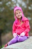 桃红色开会的逗人喜爱的小女孩在干草捆 免版税库存图片