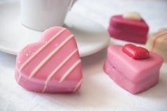 桃红色形状的心脏酥皮点心和杯子在白色na的coffe 库存照片