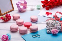 桃红色心形的蛋白杏仁饼干和婚戒与明信片,照片框架 免版税库存照片