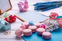 桃红色心形的蛋白杏仁饼干和婚戒与明信片,照片框架 库存图片