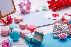 桃红色心形的蛋白杏仁饼干和婚戒与明信片,照片框架 免版税库存图片