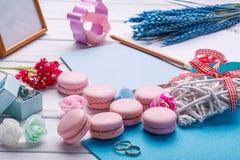 桃红色心形的蛋白杏仁饼干和婚戒与明信片 题字的地方 免版税库存图片