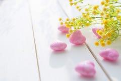 桃红色心脏和野花花束在木板的 免版税库存图片