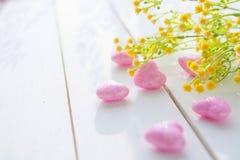 桃红色心脏和野花花束在木板的 免版税库存照片