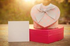 桃红色心脏礼物盒和卡片在木桌上在日落 免版税库存图片