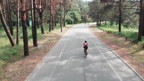 桃红色成套装备的年轻美女骑自行车者在公园骑一辆自行车 r 后侧方寄生虫视图 股票视频