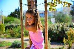 桃红色成套装备的微笑的女孩爬树 库存照片