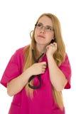 桃红色成套装备的护士有在耳朵的听诊器的查寻 免版税库存照片